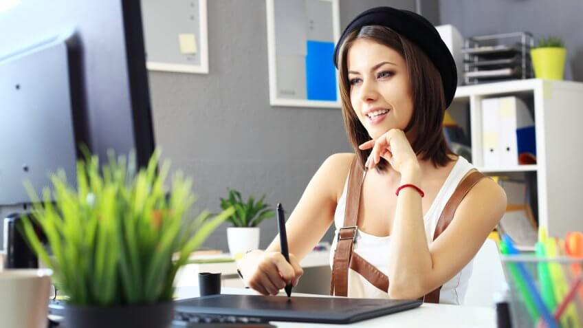 Young female designer using graphics tablet while working with computer.