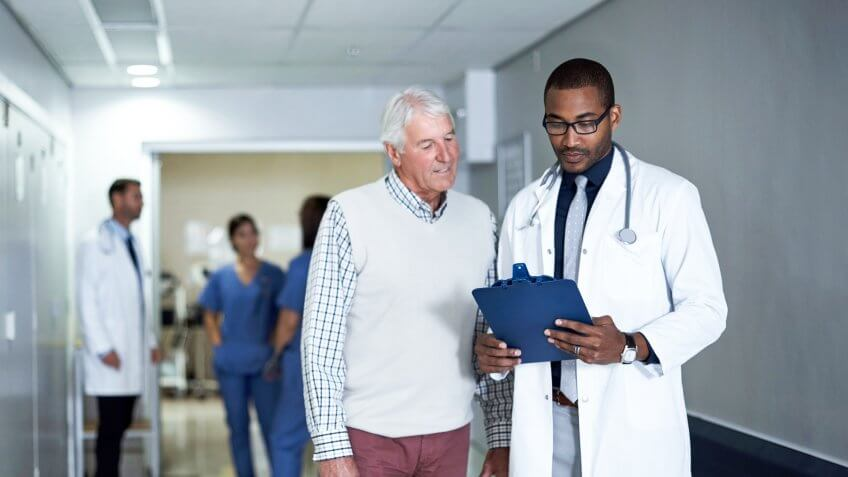 Cropped shot of a doctor talking to a senior patient while standing in the hospital corridor.
