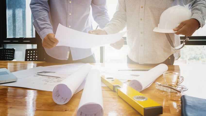 22 Industries That Pay Less (and More) Than They Did 10 Years Ag, Architects concept, Architects working with blueprints in the office