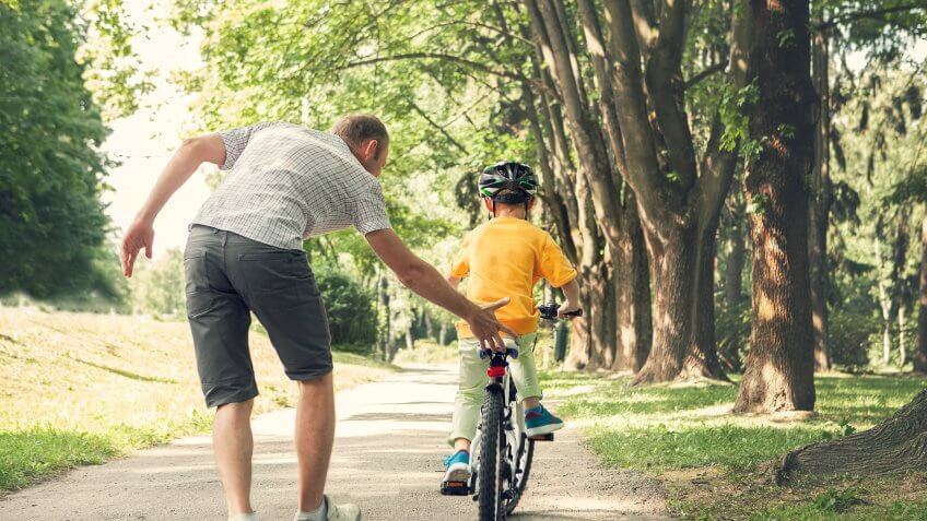 son with helmet riding bicycle with father