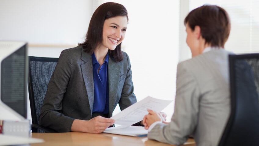 Businesswomen with paperwork talking face to face.