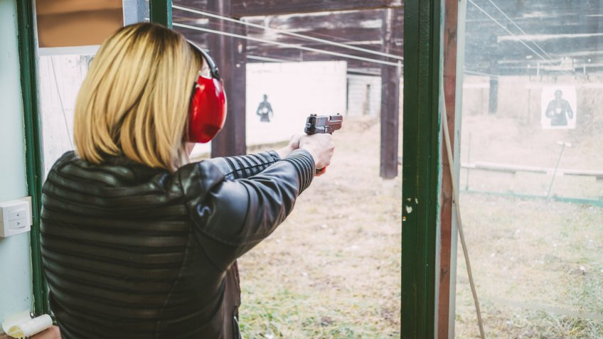 96 Money-Making Skills You Can Learn in Less Than a Year, Woman firing with pistol on target at the shooting range. Rear v
