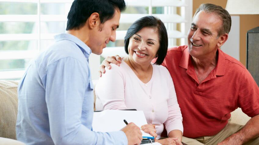 Financial Advisor Talking To Senior Couple At Home Writing Documents Smiling.