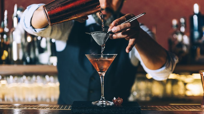 96 Money-Making Skills You Can Learn in Less Than a Year, Expert barman is making cocktail at night club.