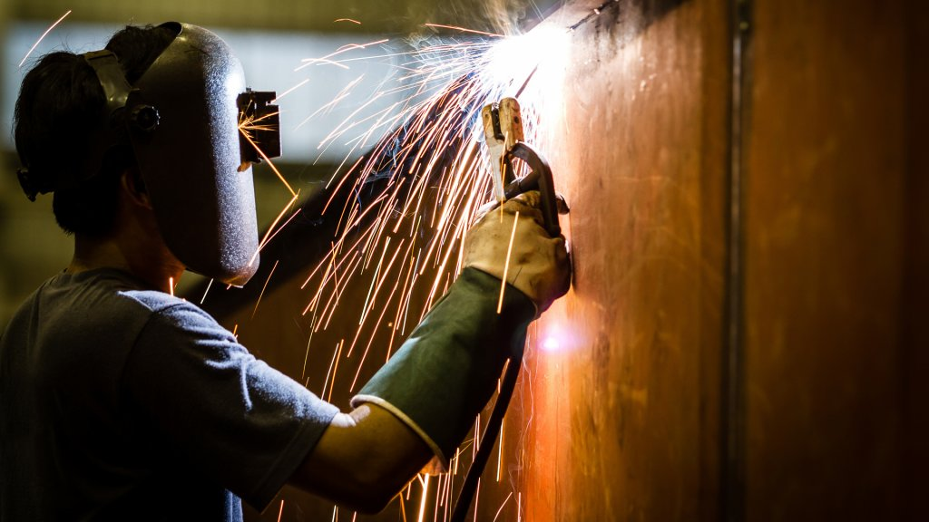 96 Money-Making Skills You Can Learn in Less Than a Year, worker with protective mask welding metal and sparks