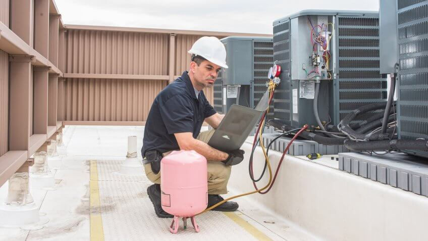 96 Money-Making Skills You Can Learn in Less Than a Year, Technician looking at a panel off a condensing unit.