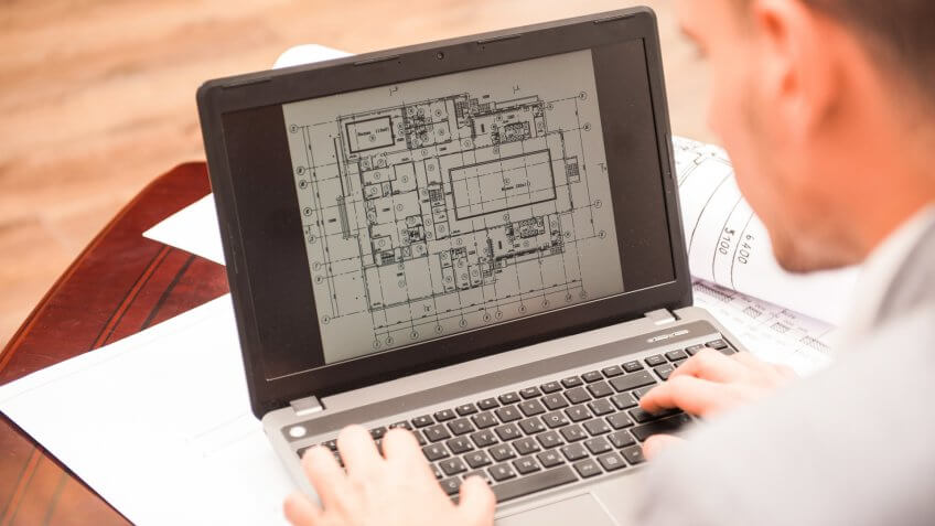 96 Money-Making Skills You Can Learn in Less Than a Year, Close-up portrait of laptop with blueprints, architect sitting from behind working on architectural plan, interior shot