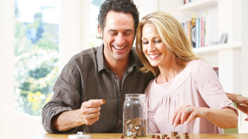Middle aged couple counting coins into jar.