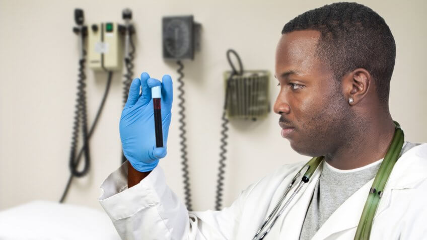96 Money-Making Skills You Can Learn in Less Than a Year, A black man African American doctor holding a test tube vial sam