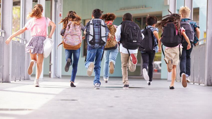students with backpacks running in school
