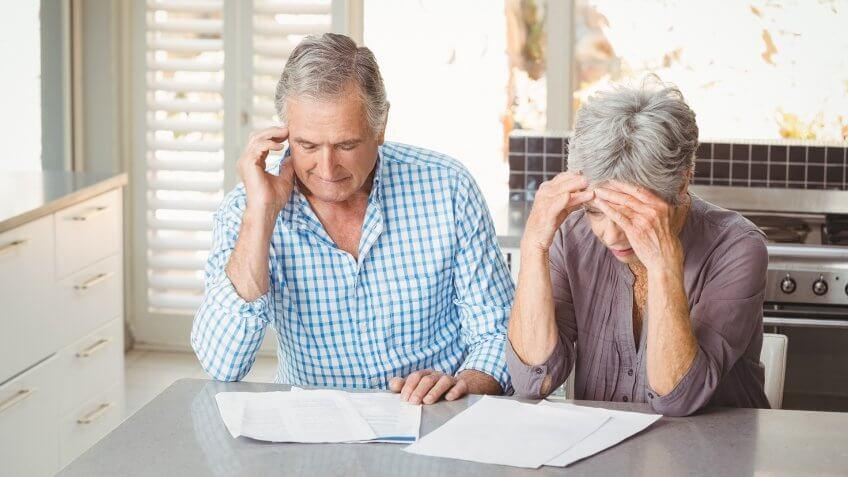 Worried senior couple with documents sitting in kitchen at home