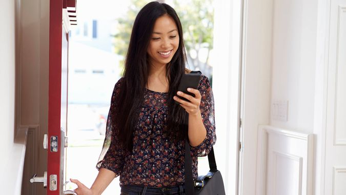 Woman Opening Front Door Whilst Checking Mobile Phone.