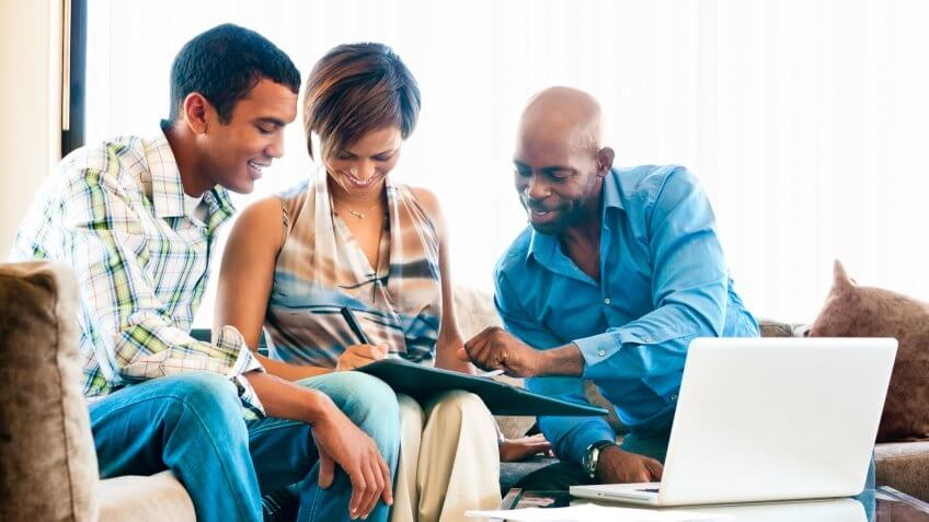 Young African couple in a meeting with a financial advisor signing documents.