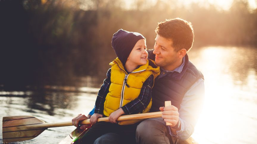 Dad and son enjoying canoe ride on a beautiful sunny day,.