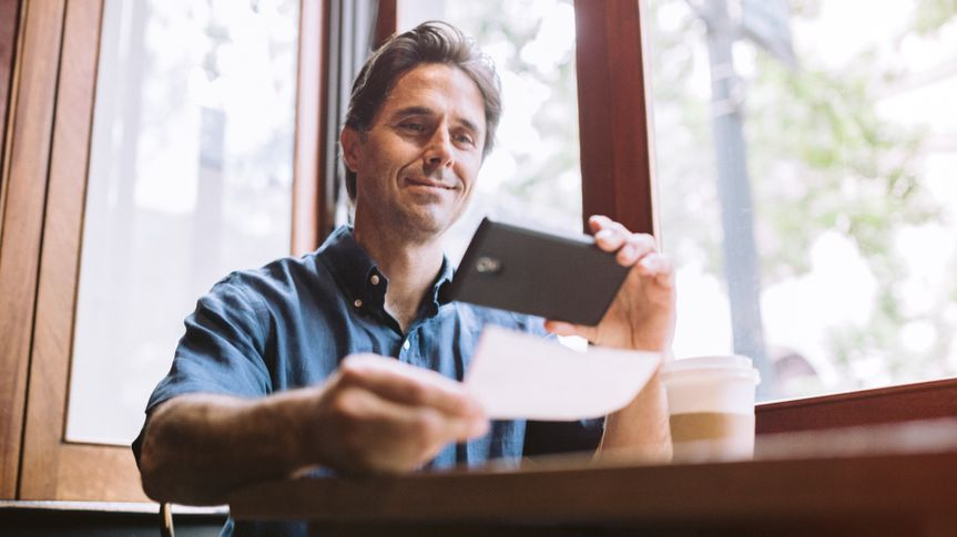 """A mature smiling man in his mid 40's takes a picture with his smart phone of a check or paycheck for digital electronic depositing, also known as """"Remote Deposit Capture""""."""