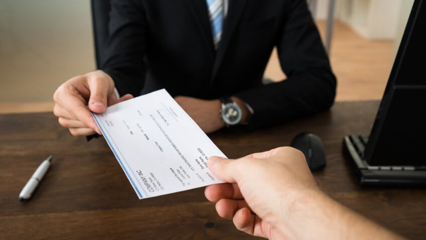 Close-up Of Businessman Hands Giving Cheque To Other Person In Office.
