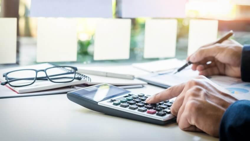 Business finance man calculating budget numbers, Invoices and financial adviser working., Secret Tips to Live a Financially Secure Life
