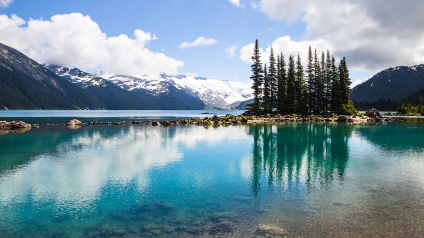The clear, tranquil waters of Garibaldi Lake in Garibaldi Provincial Park near Whistler in British Columbia, produce bottle-green reflections of an island of conifers.