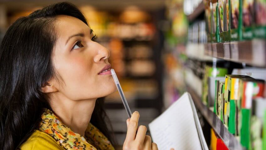 Thoughtful woman shopping for grocery in supermarket.