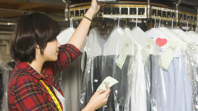 Female owner reading receipt by clothes rail in laundry