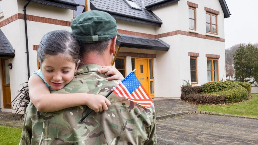 Composite images of American soldier carrying girl in front of a house.