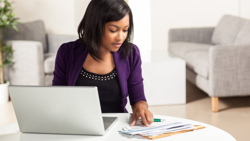 Attractive young African American woman working on finances at h, Secret Tips to Live a Financially Secure Life