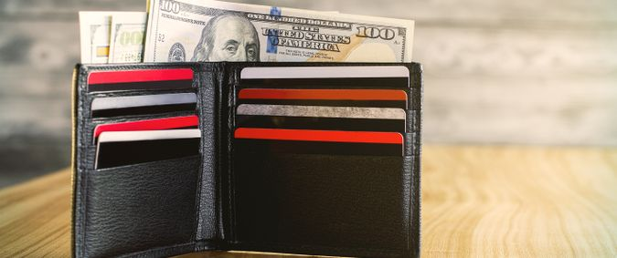 Open black wallet wth dollars and plastic cards on wooden table.