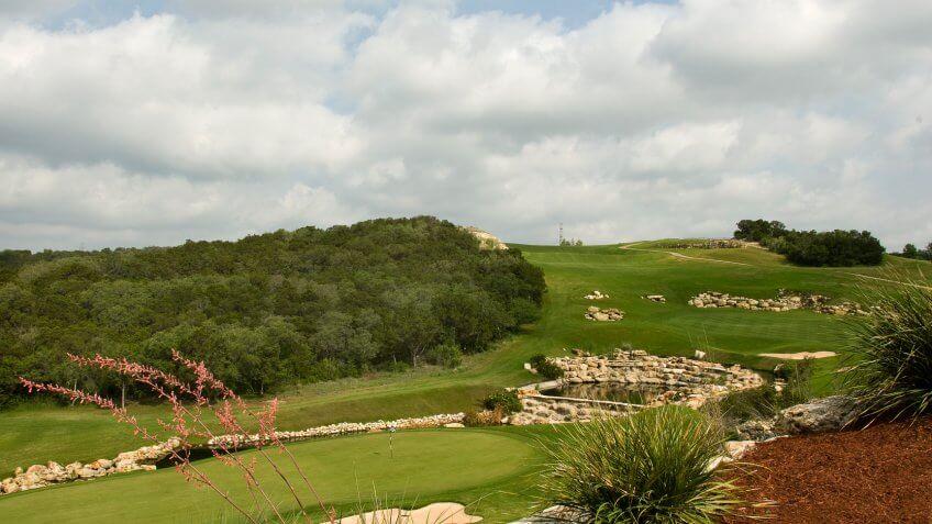 """photograph of La Cantera Golf Club, Palmer Golf Course, Hole 9, San Antonio, Texas, with fairway, putting green, Rocks, Ponds, flag, blue sky, trees""."