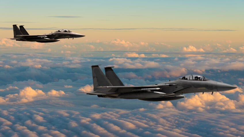 F-15 Eagle fighter jets flying above clouds.