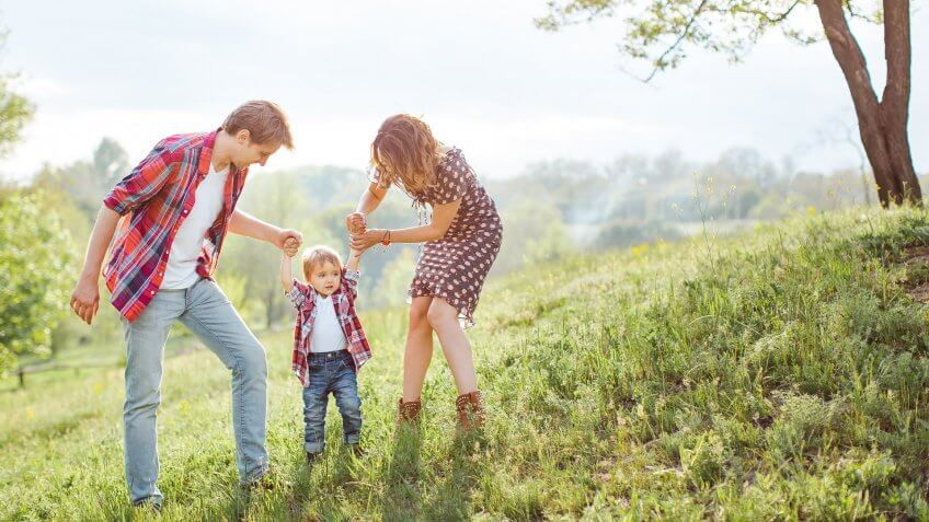 Photo of a young family enjoying holidays in the park on a sunny summer day near big family tree countryside.