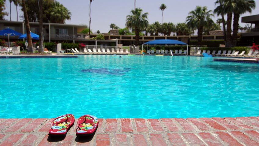 """""""Sandals Next To Large Empty Swimming Pool In Palm Springs, California""""."""