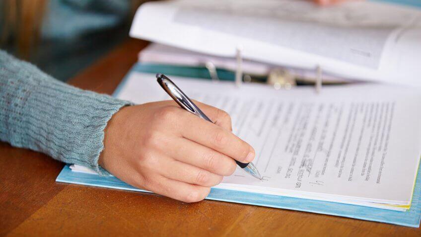 Close up of a teacher marking a test.