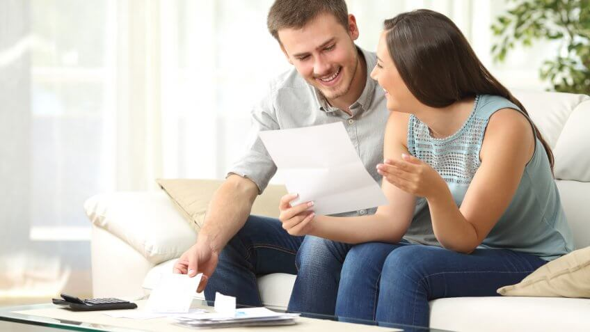 Happy couple reading mail and checking accountancy looking each , Secret Tips to Live a Financially Secure Life