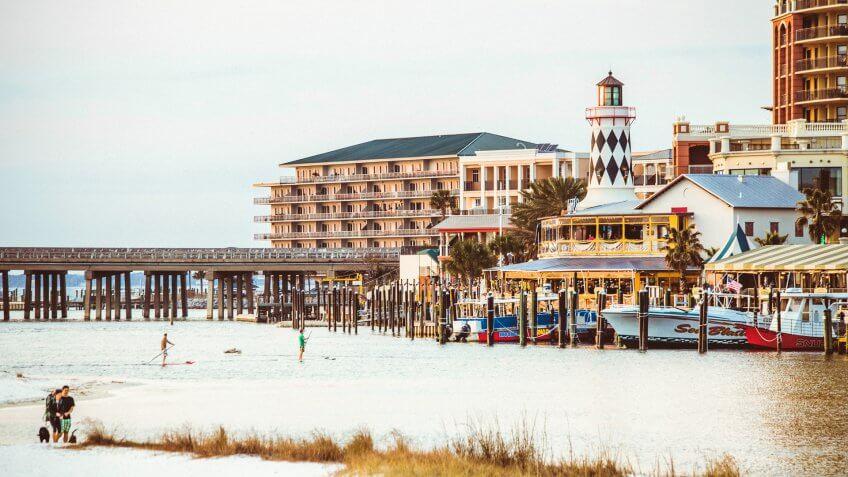 Destin, Florida, US - February 26, 2014: People enjoying a sandy beach at sunset time, Harborwalk Marina in background.