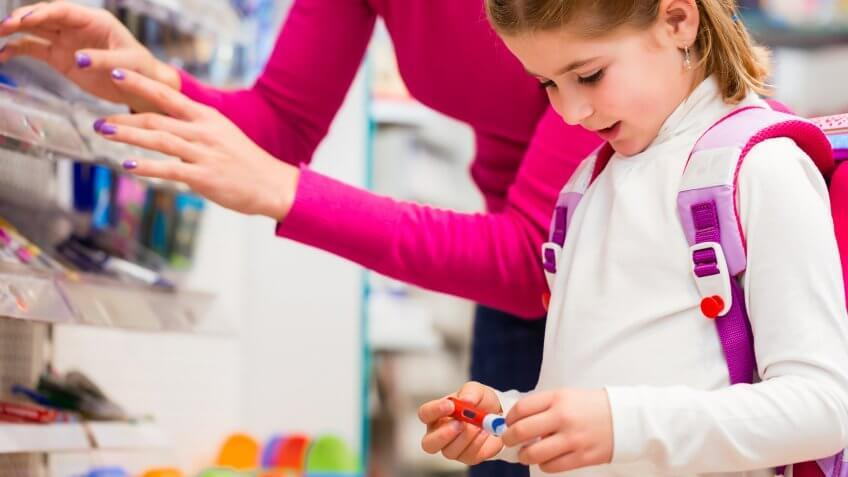Family buying school supplies in stationery store, little girl looking at a fountain pen.