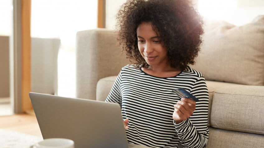 Shot of a young woman using her credit card to make an online payment at homehttp://195.