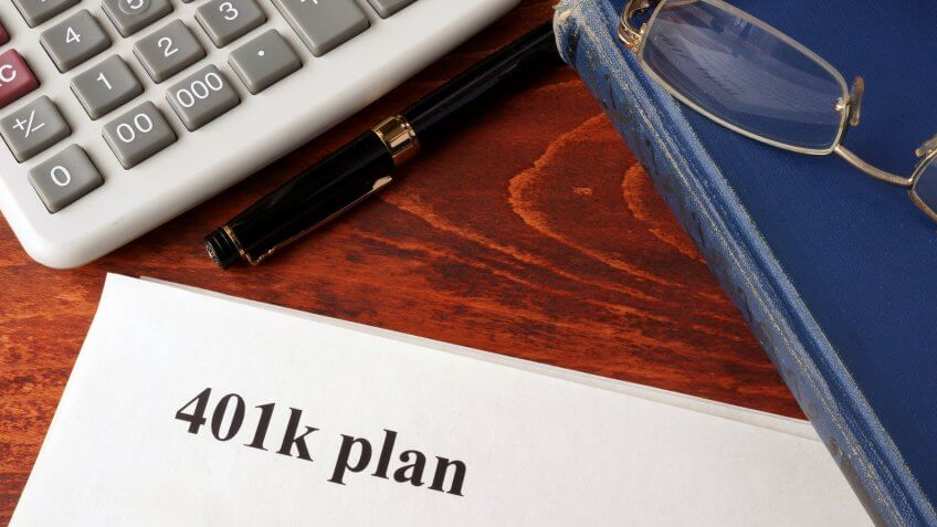 Papers with 401k plan and book on a table.