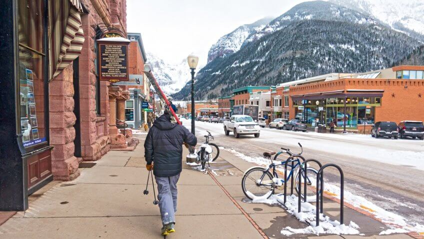Skier Walks the Streets of Telluride, Colorado With His Skis, Boots, and Poles.