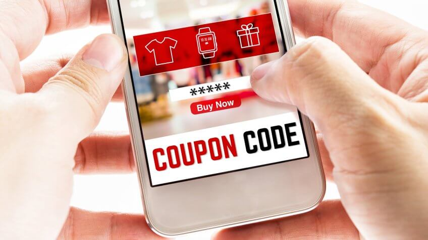 Close up Two hand holding mobile phone with coupon code word and blurred store background, Digital Marketing concept.