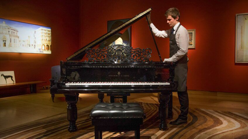 LONDON, ENGLAND - FEBRUARY 17:  A member of staff opens the lid as he poses with a Steinway ebonised 'Model B' grand piano at Christie's auction house on February 17, 2016 in London, England.