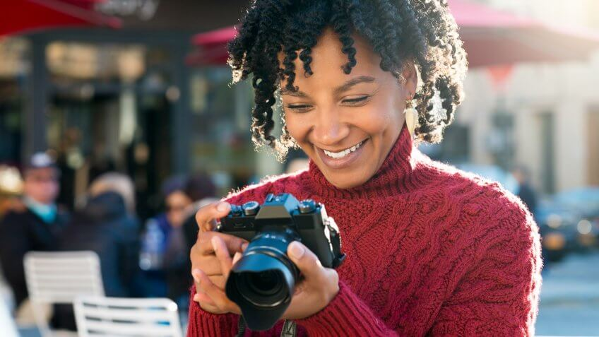 Portrait of tourist with digital camera at cafe.