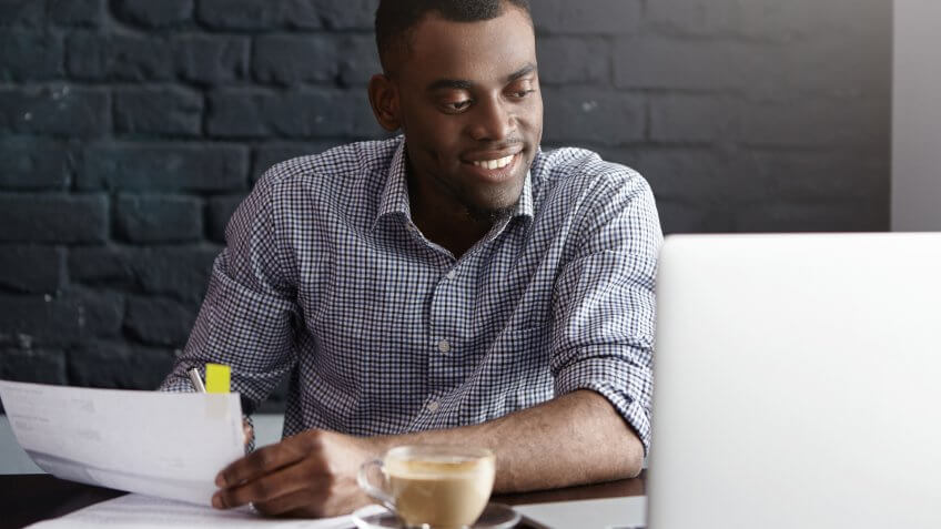 businessman in formal wear filling in papers while managing finances at cafe during lunch break, sitting at table in front of open laptop, having cappuccino
