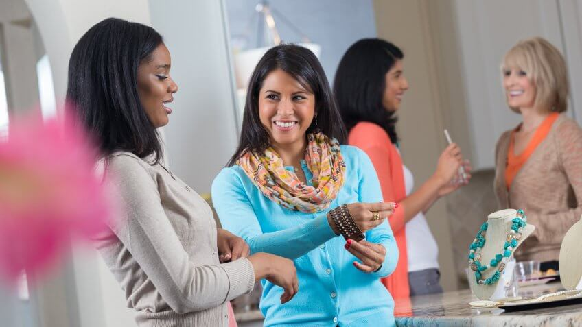 Diverse group of women trying on jewelry at home party.