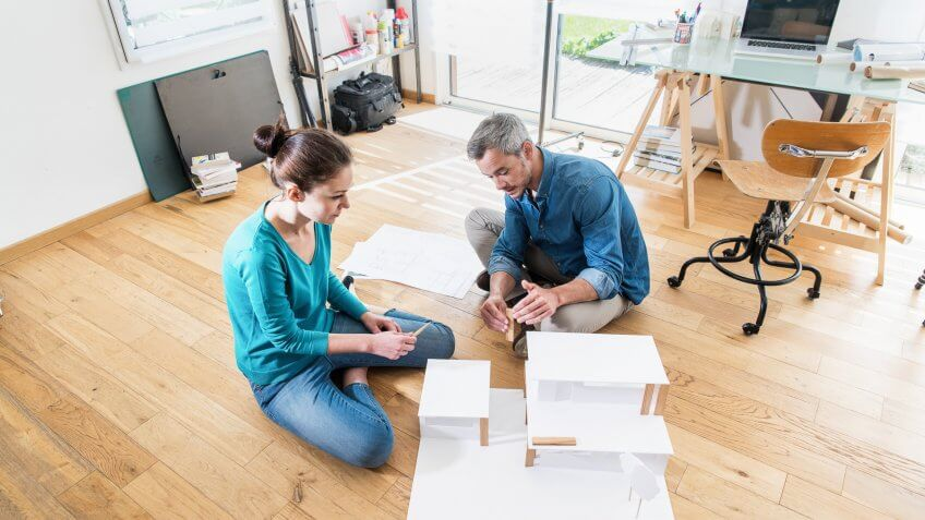 Top view. Two architects, a man and a woman working on a construction project in the office. They sit on the floor and finalize a model house.
