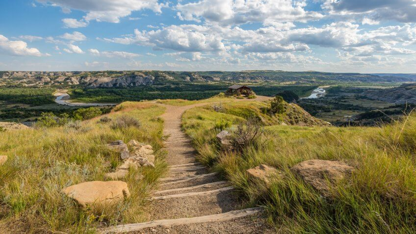A trail to a scenic overlook of a badlands river valley.