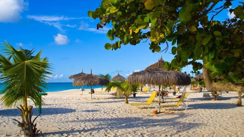 Beautiful beach with palapas and palmtrees, Eagle Beach, Aruba.