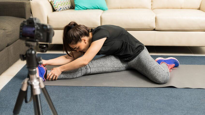 Young woman in sporty outfit doing some stretching exercises and recording it on camera