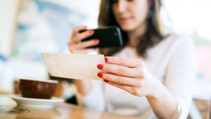 """11730, 20-29 Years, A smiling young woman takes a picture with her smart phone of a , Bank Deposit Slip, Cafe, Check - Financial Item, Coffee Shop, Currency, E-commerce, Electronic Banking, Horizontal, Paycheck, Paying, Photographing, Smart Phone, Smiling, Women, Young Adult, also known as """"Remote Deposit Capture"""".  She sits in a coffee sh, depositing, enjoying an espresso latte.  Bright sunlight shines in the windo, people"""