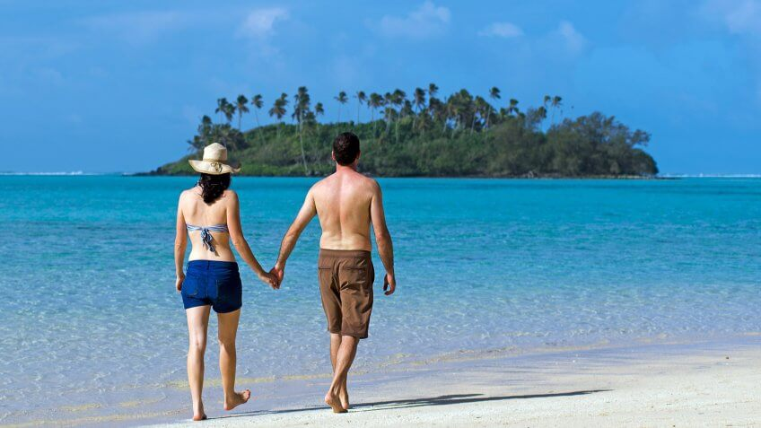 Attractive young happy couple on vacation walks on a beach of Pacific Island.