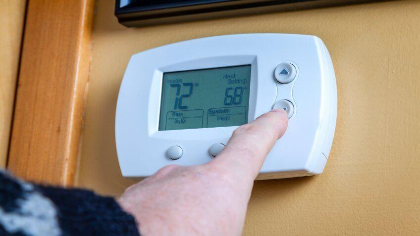 Energy saving, finger on thermostat